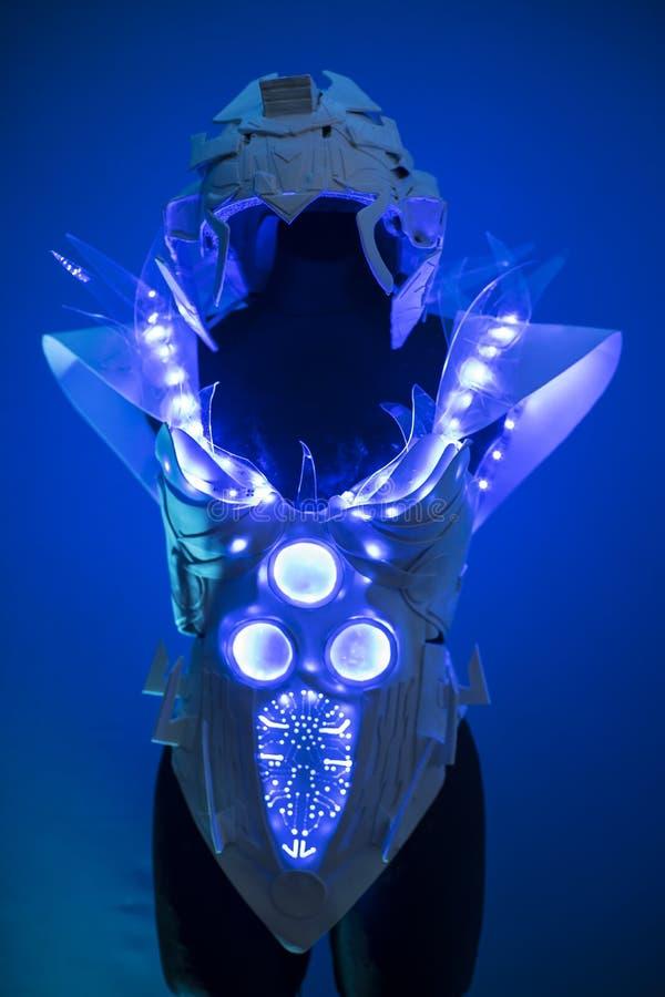 靠机械装置维持生命的人、利用仿生学的装甲有蓝色LED光的和塑料材料 库存照片