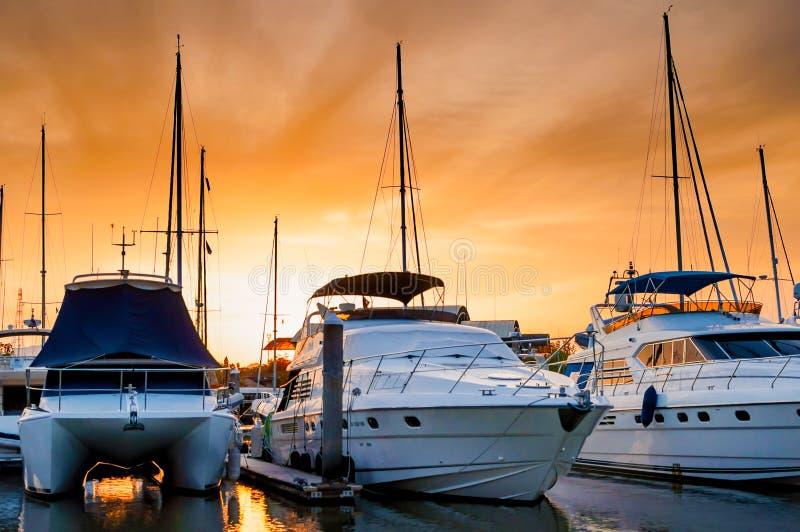 靠码头在小游艇船坞的游艇和小船在晚上 免版税库存照片
