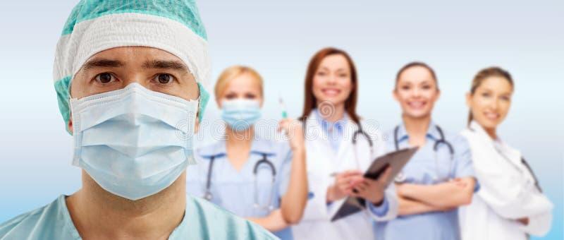 面具的外科医生与小组在蓝色的军医 免版税库存图片
