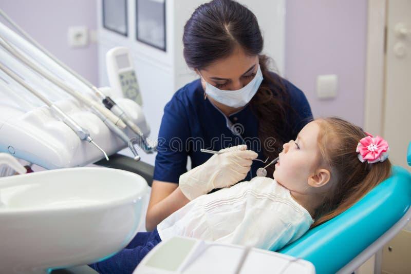 面具的女性牙医对待牙小女孩 免版税库存图片