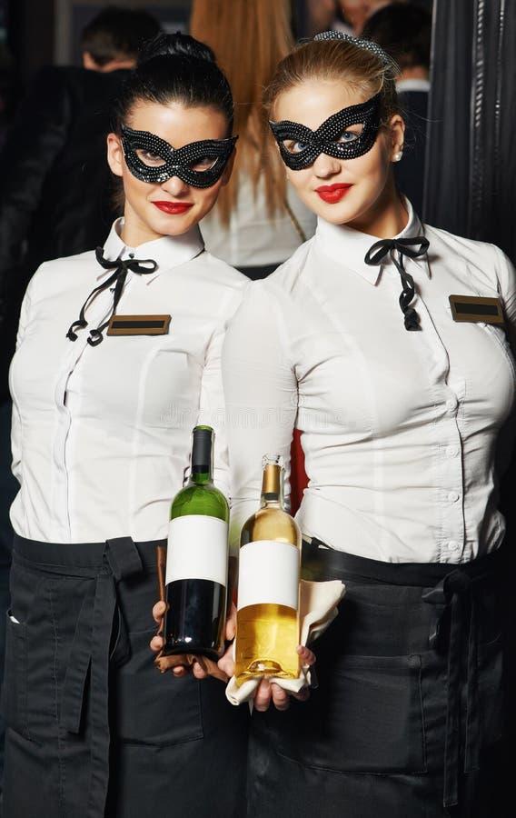 面具的女服务员女孩与瓶 库存图片