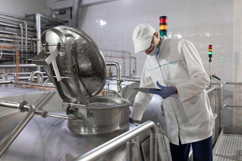 面具的审查员和在他的手上洗刷站立与一种文件夹片剂在牛奶店 库存照片