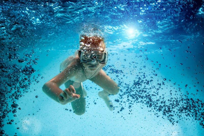 面具的少年和废气管游泳在水面下。 免版税库存图片