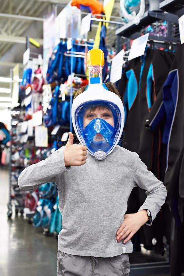 面具的男孩佩戴水肺的潜水的在体育商店 库存图片