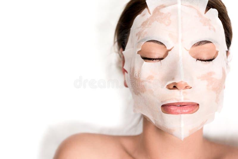 面具的美丽的少妇在放松与在温泉沙龙的闭合的眼睛的面孔 免版税库存照片