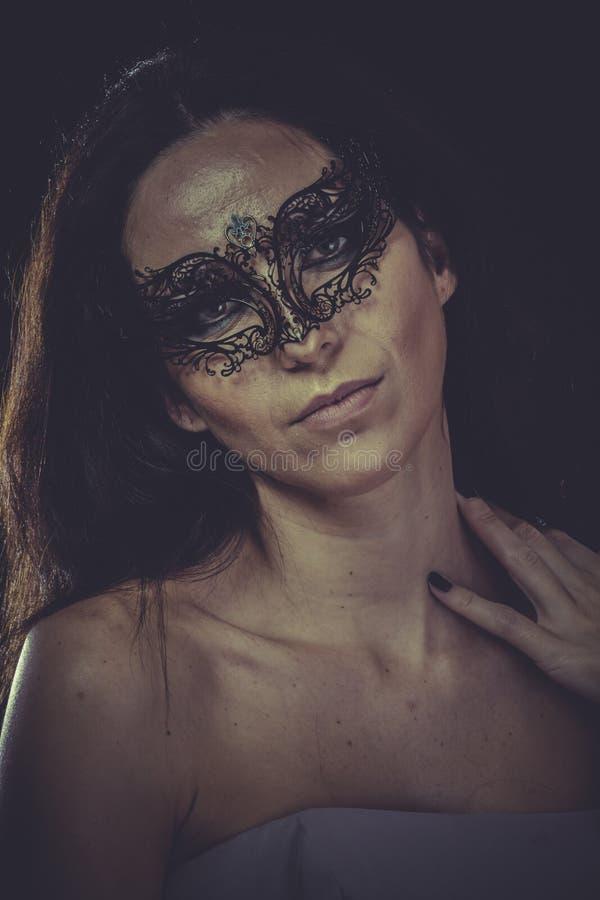 黑面具金属褶边的深色的妇女 库存照片