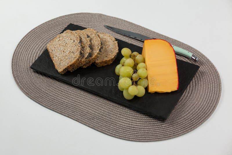 黑面包、葡萄和荷兰扁圆形干酪与刀子在板岩上 免版税库存照片