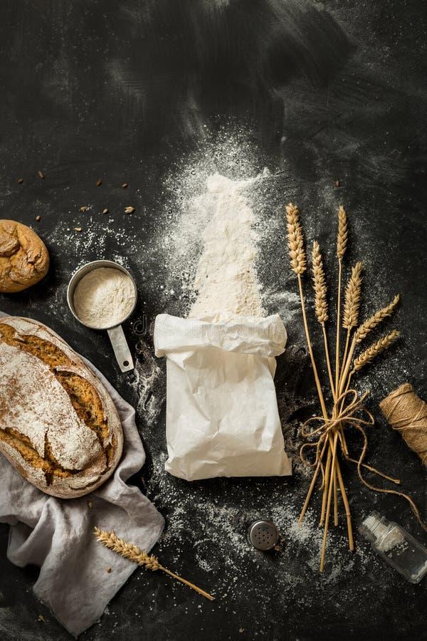 面包、面粉袋子、麦子和量杯在黑色 库存照片