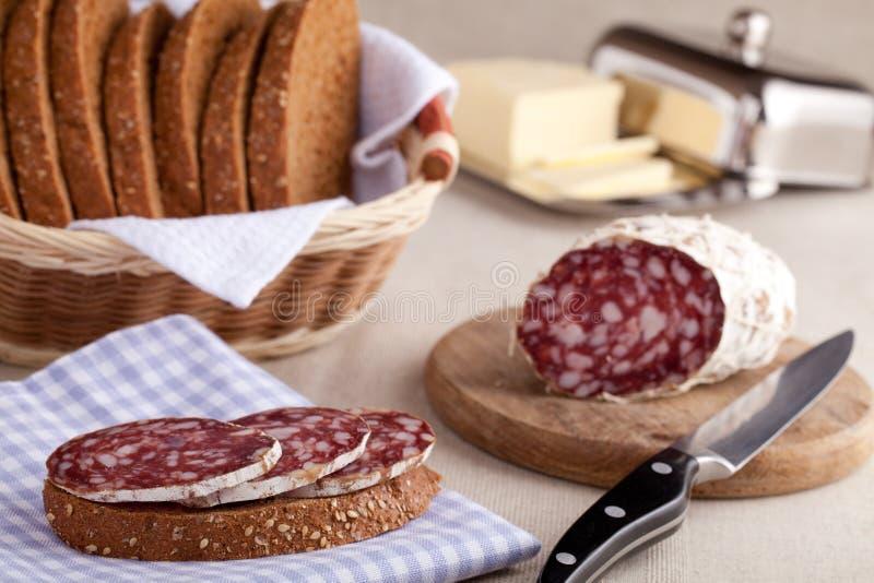 面包厨房蒜味咸腊肠三明治服务的表 免版税库存图片