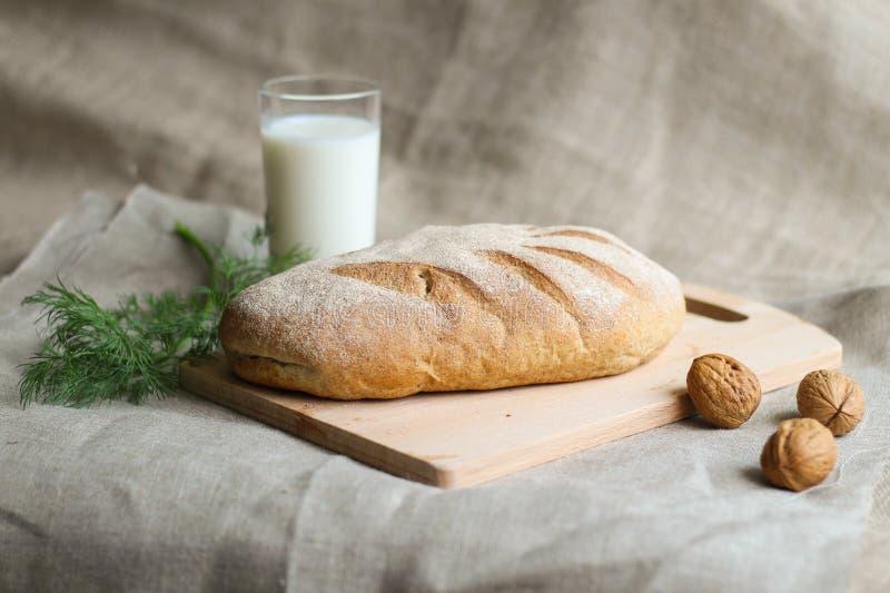面包和牛奶用核桃和莳萝在一个木板 免版税库存照片