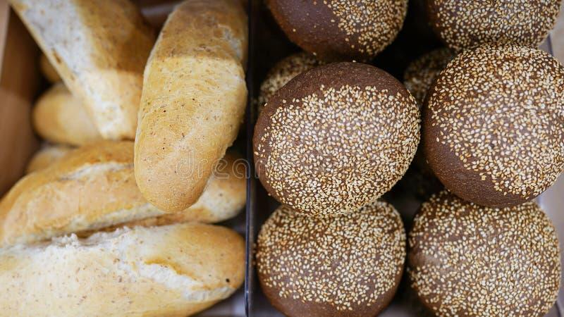 面包和许多在一个篮子的新鲜面包小圆面包在一张木桌上 免版税库存照片