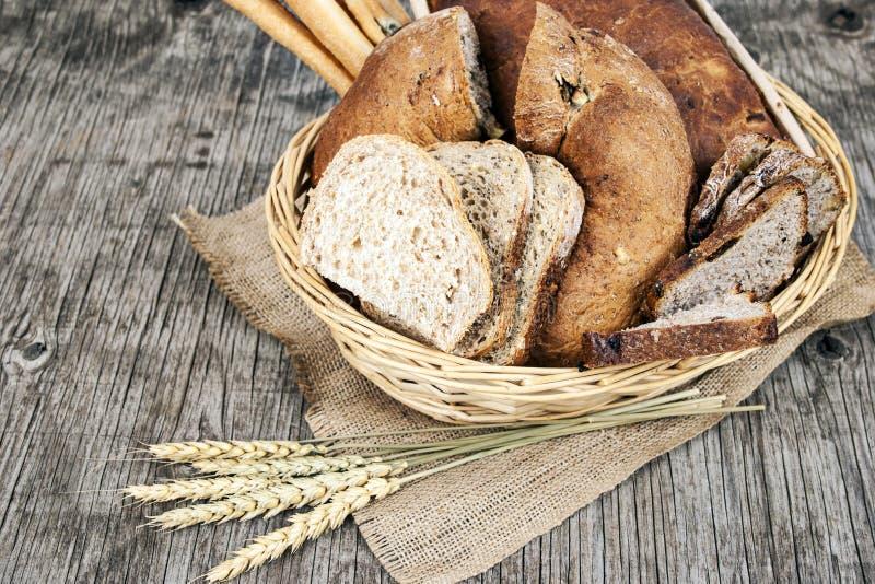 面包和谷物在木葡萄酒背景 免版税库存图片