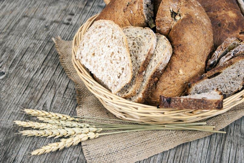 面包和谷物在木葡萄酒背景 免版税库存照片