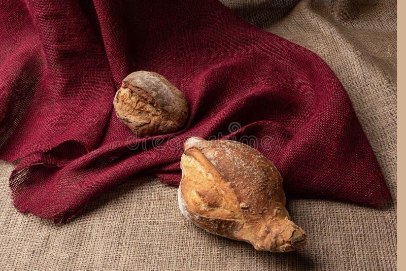 面包在桌上的以五颜六色的粗麻布,静物画,特写镜头为背景 免版税库存图片
