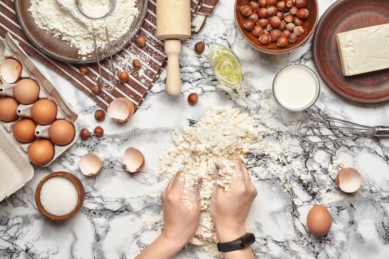 : 面包师厨师位置的顶视图,手与在大理石桌背景的未加工的面团一起使用 免版税库存图片