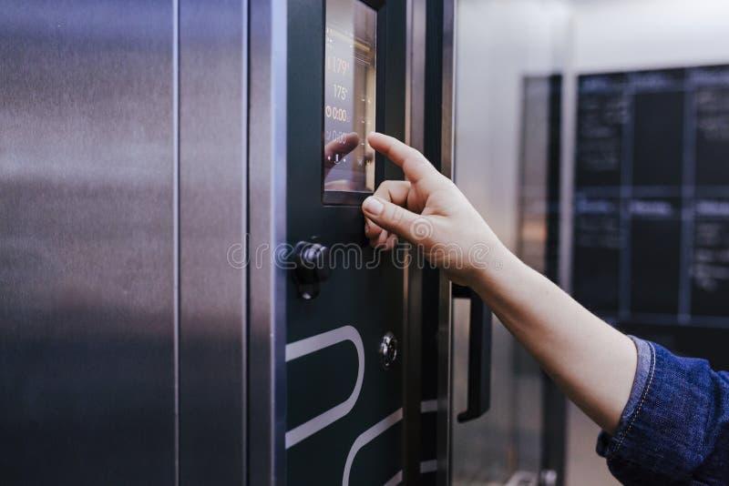 面包师妇女的手使用烤箱机器的在面包店 免版税库存照片