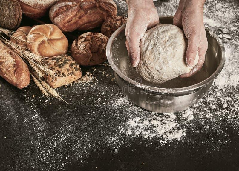 面包师揉的面团的手在碗的 免版税库存照片