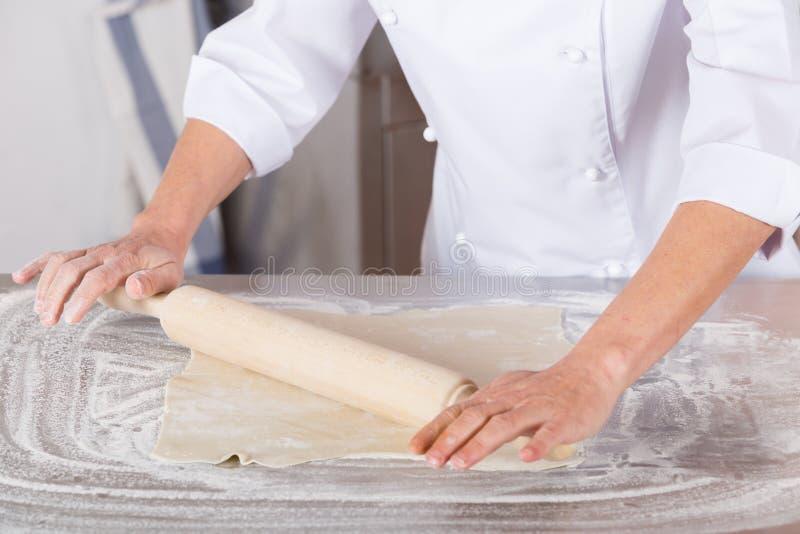 面包师面团递做展开的揉的大面包 免版税库存照片