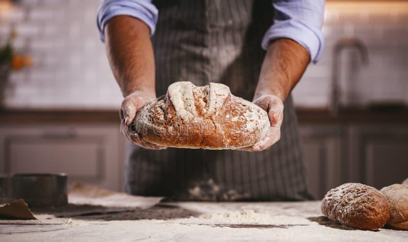 面包师` s男性的手揉面团 图库摄影
