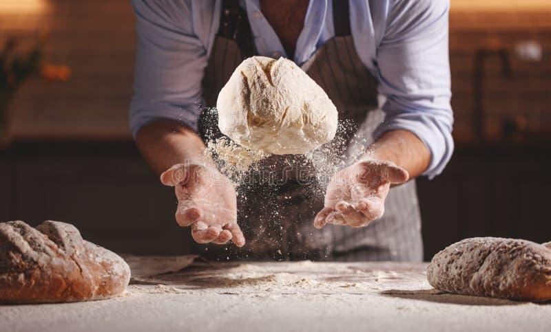 面包师` s男性的手揉面团 库存图片