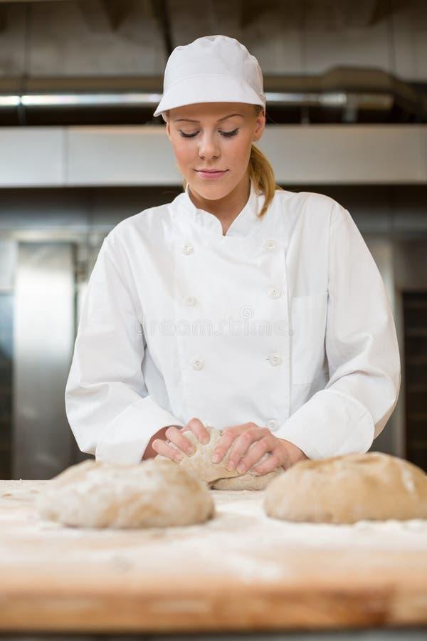 面包店或面包店揉的面团的贝克 免版税库存图片