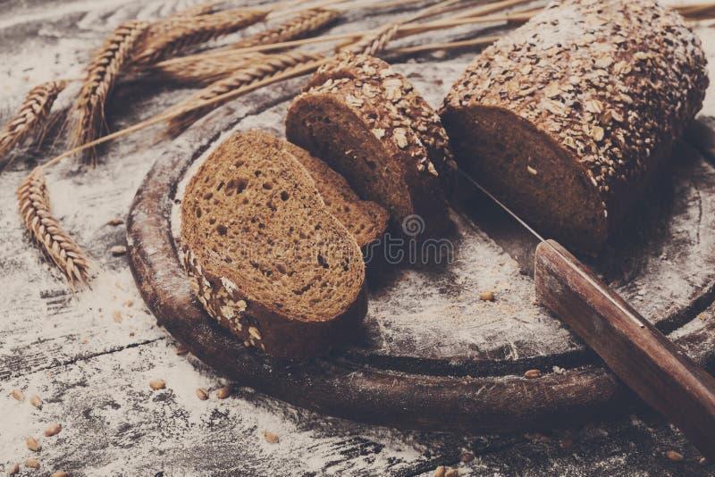 面包店概念背景 整个五谷切的面包和刀子 免版税库存照片