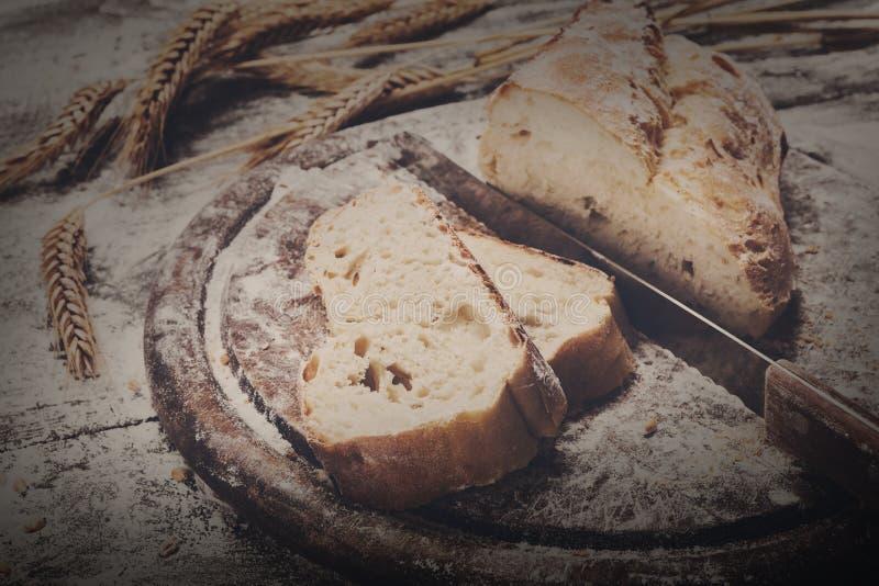 面包店概念背景 整个五谷切的面包和刀子 免版税库存图片