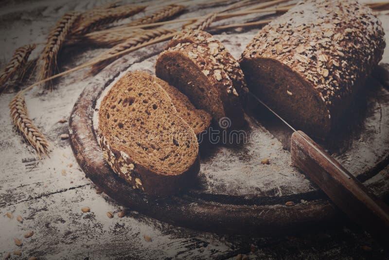 面包店概念背景 整个五谷切的面包和刀子 图库摄影