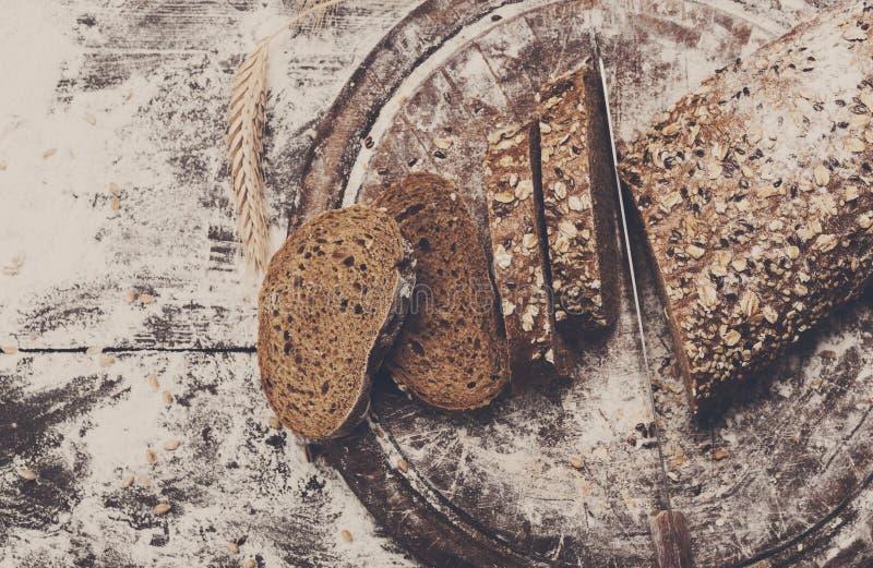 面包店概念背景 整个五谷黑麦切的面包和刀子 库存照片