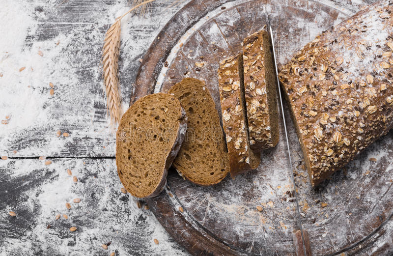 面包店概念背景 整个五谷黑麦切的面包和刀子 图库摄影