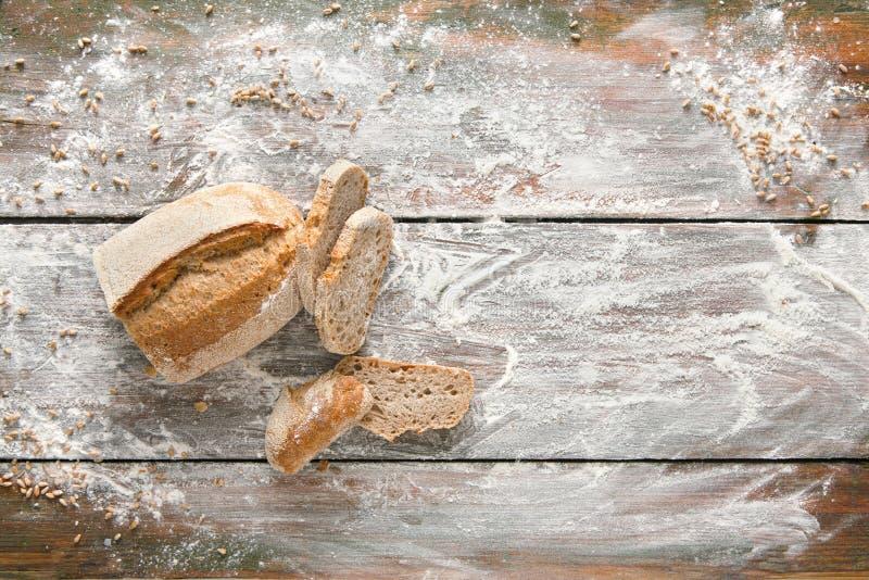 面包店概念背景 白色在土气木头的切的面包 免版税库存照片