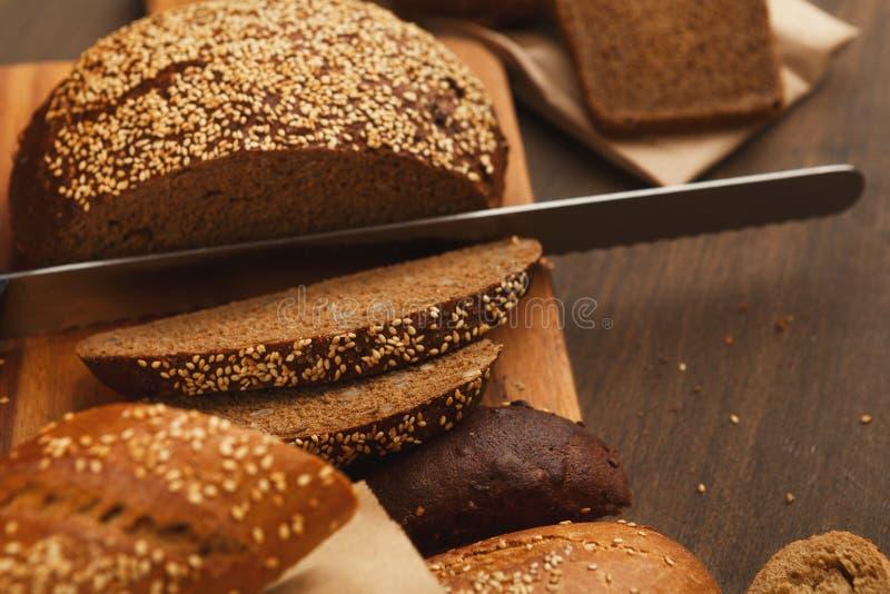 面包店概念 在船上切与刀子的面包 免版税库存图片