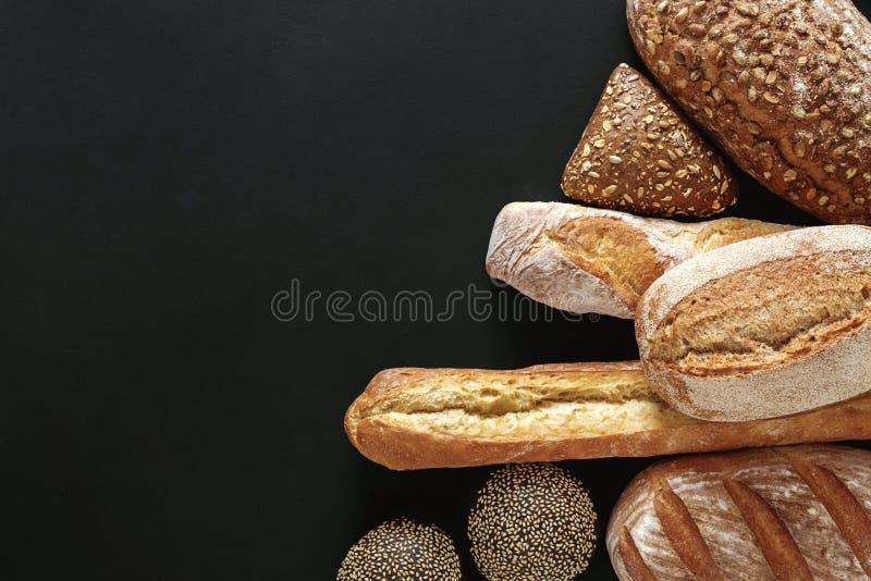 面包店概念 在balck面包背景隔绝的大量 免版税库存照片