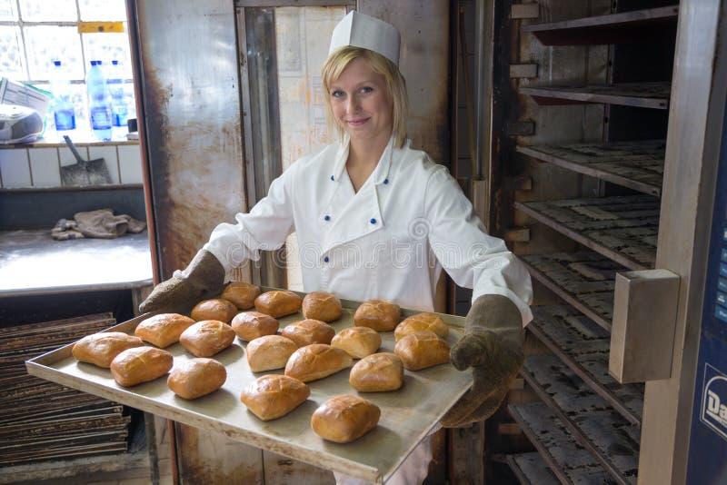 面包店的投入面包的贝克或面包店在烤箱 免版税库存照片