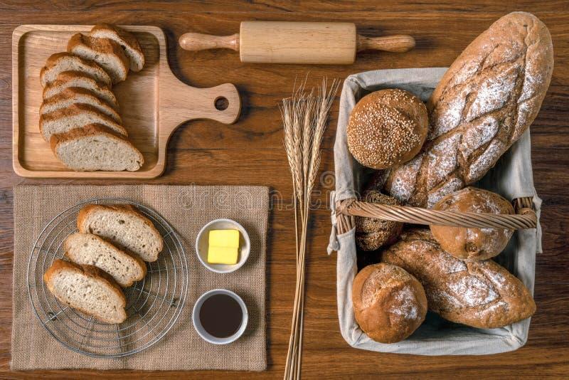 面包店面包的分类食物背景在篮子的用在木板材的切的谋生和巧克力汁 免版税库存图片