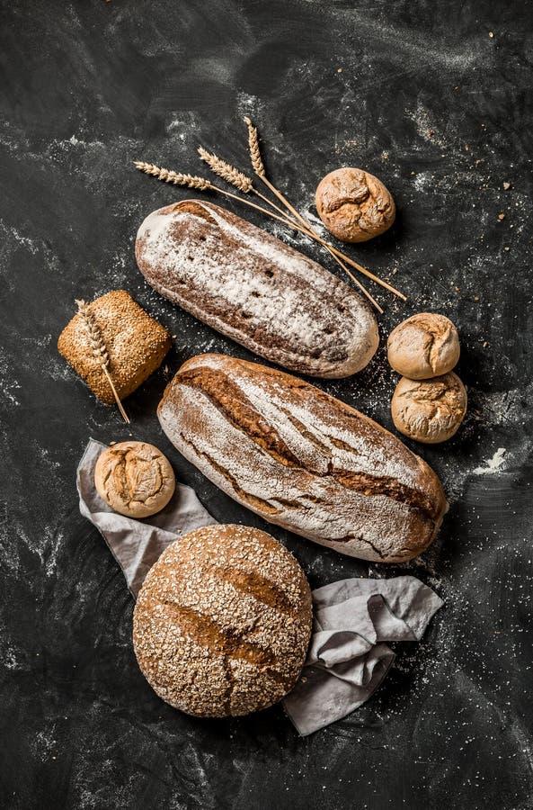 面包店-土气有壳的面包和小圆面包在黑色 库存图片