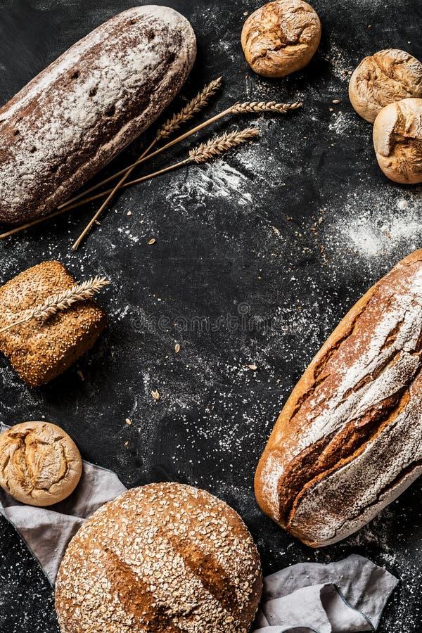 面包店-土气有壳的面包和小圆面包在黑色 免版税图库摄影