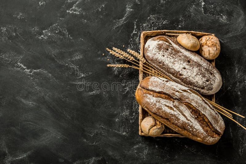 面包店-土气有壳的面包和小圆面包在黑色 免版税库存照片