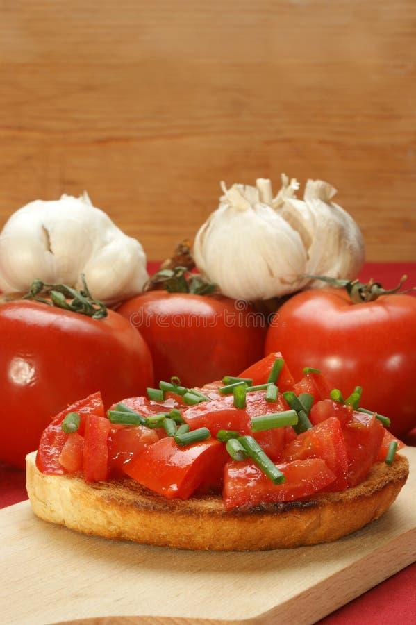面包把敬酒的蕃茄切成小方块 免版税库存图片
