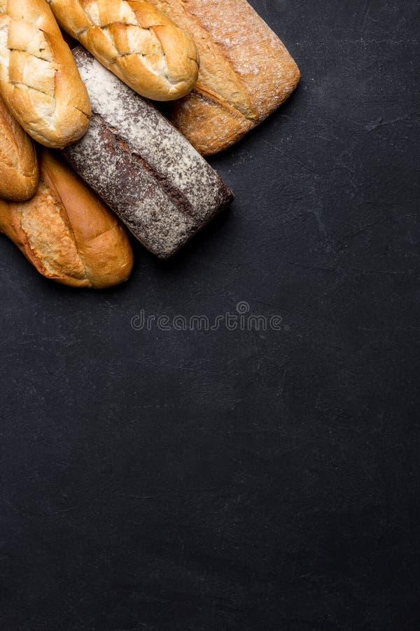 面包混杂的品种在黑暗的桌上的 r 库存图片