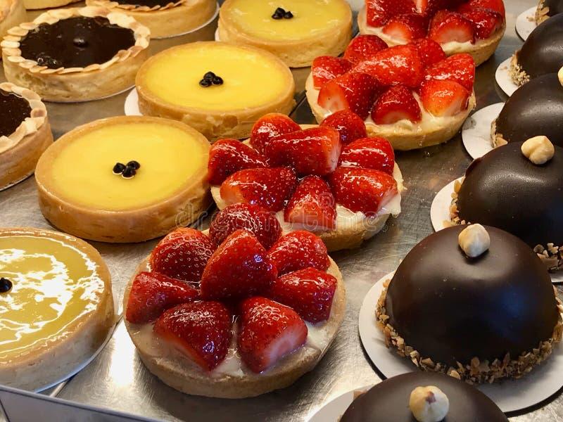 面包点心店以馅饼,蛋糕,焦糖奶油品种,当草莓、巧克力、柠檬、梨和苹果切片被显示在sho 库存照片