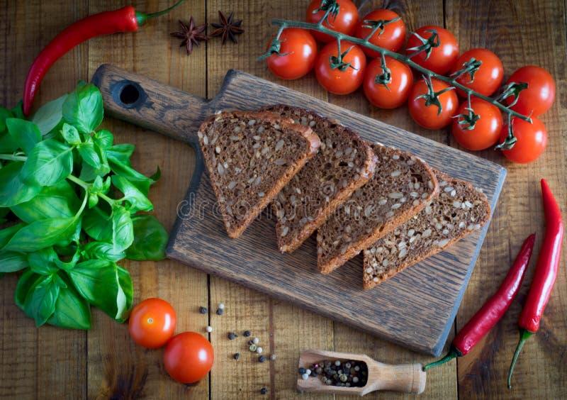 面包片在一切板、新鲜的蕃茄、芬芳蓬蒿和辣子的在一张木桌上 库存图片