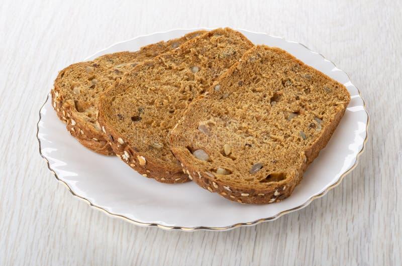面包片用不同的种子,脯,在板材的黑麦麸皮的在木桌上 库存图片