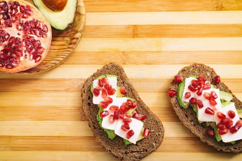 面包片用鲕梨、西红柿、石榴种子和新鲜的干酪 免版税库存照片