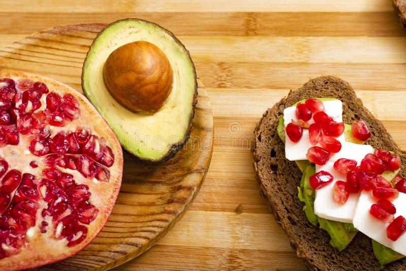 面包片用鲕梨、西红柿、石榴种子和新鲜的干酪 库存图片