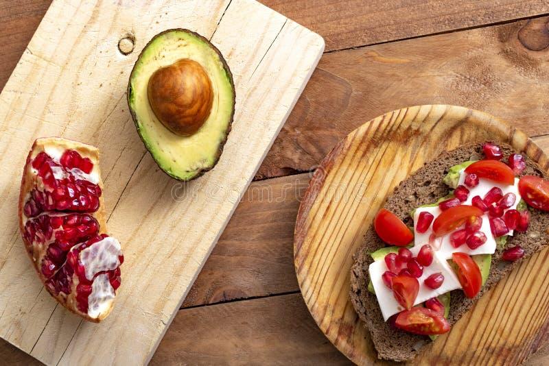 面包片用鲕梨、西红柿、石榴种子和新鲜的干酪 免版税图库摄影