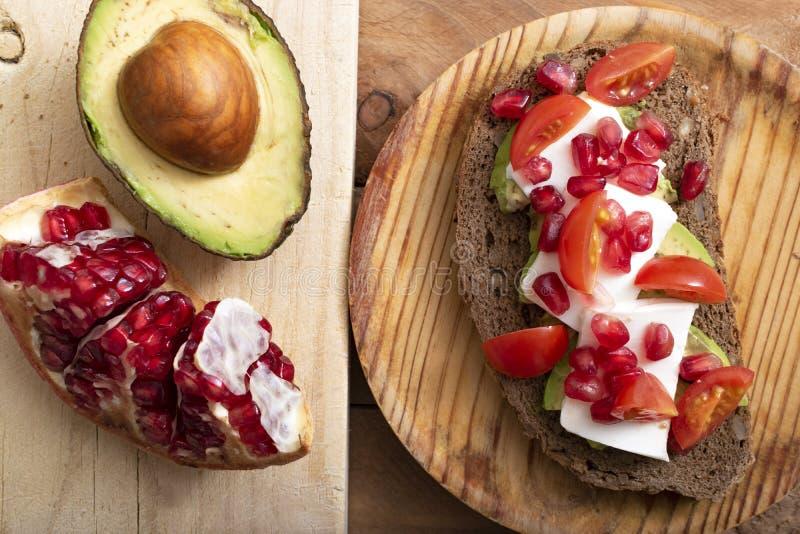 面包片用鲕梨、西红柿、石榴种子和新鲜的干酪 库存照片