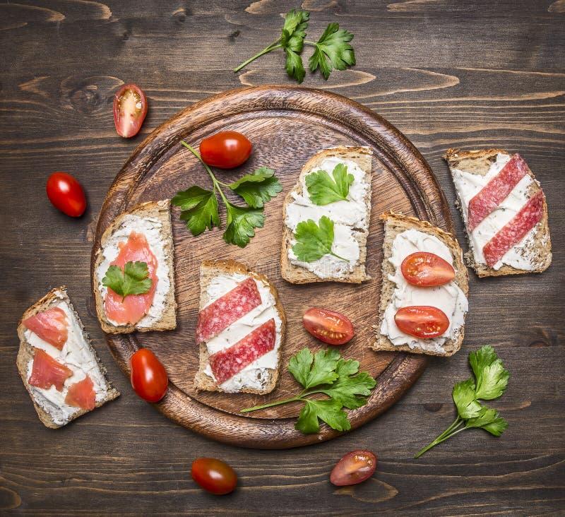 面包用乳酪蕃茄用在一个切板的草本在木土气背景顶视图 库存图片