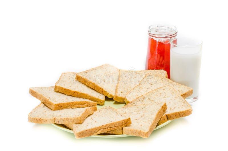 面包用牛奶果酱在白色演播室的 免版税库存照片