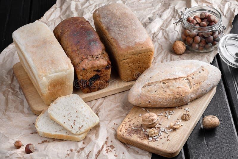 面包的不同的类型从面包店的,在一个木橡木板的谎言 在核桃和榛子附近 免版税库存图片